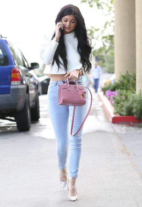 mujer en la calle con pantalon azul lavanda y blanco