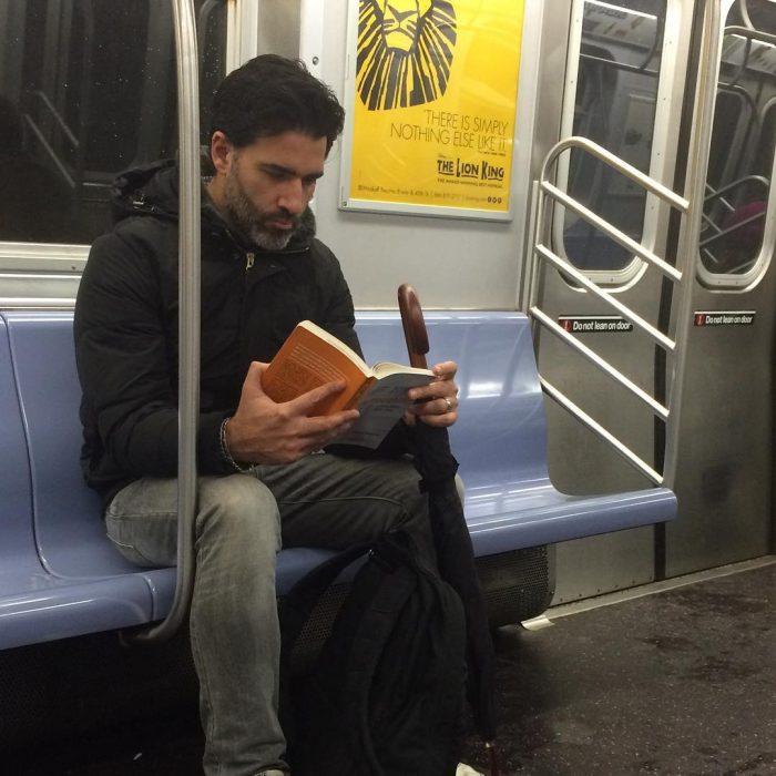 hombre con sudadera sentado leyendo un libro