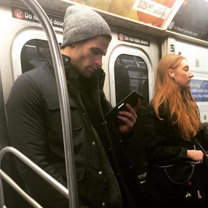 hombre de gorra gris leyendo un libro en el metro