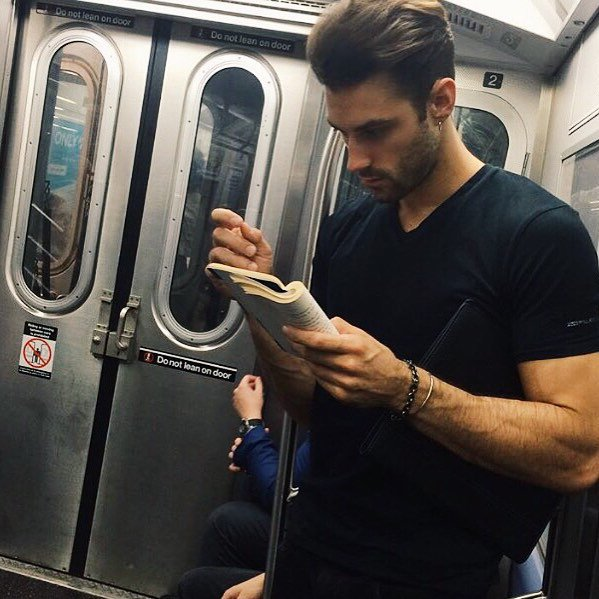 hombre de playera negra con libro leyendo en el metro
