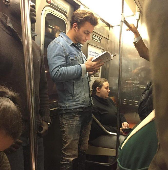 hombre rubio leyendo un libro de pie
