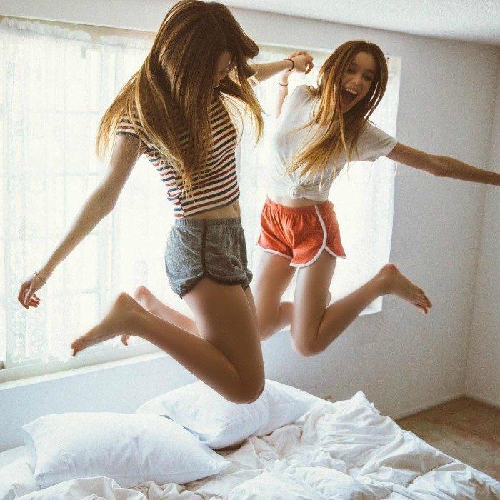 chicas saltando en la cama sonrien