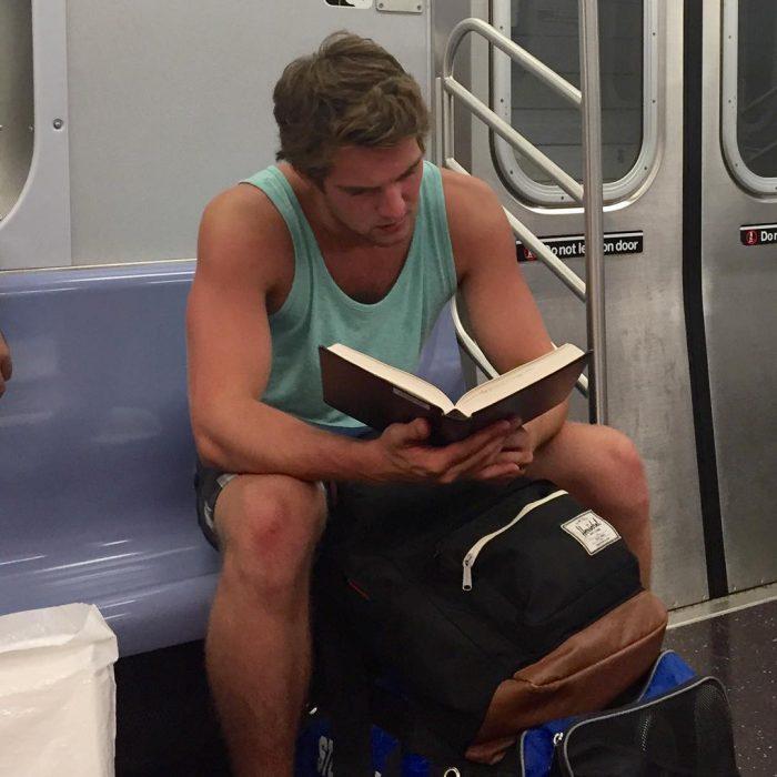 hombre con playera azul leyendo un libro