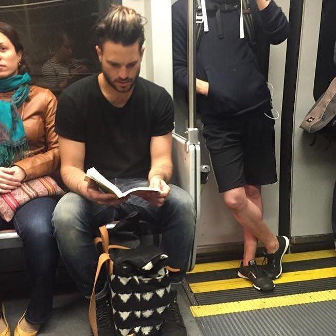 hombre de playera negra leyendo un libro en el metro