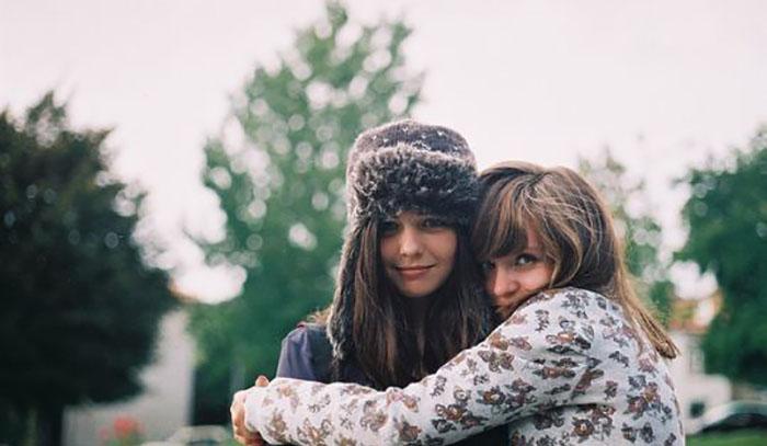 chica abrazando a su amiga con gorro