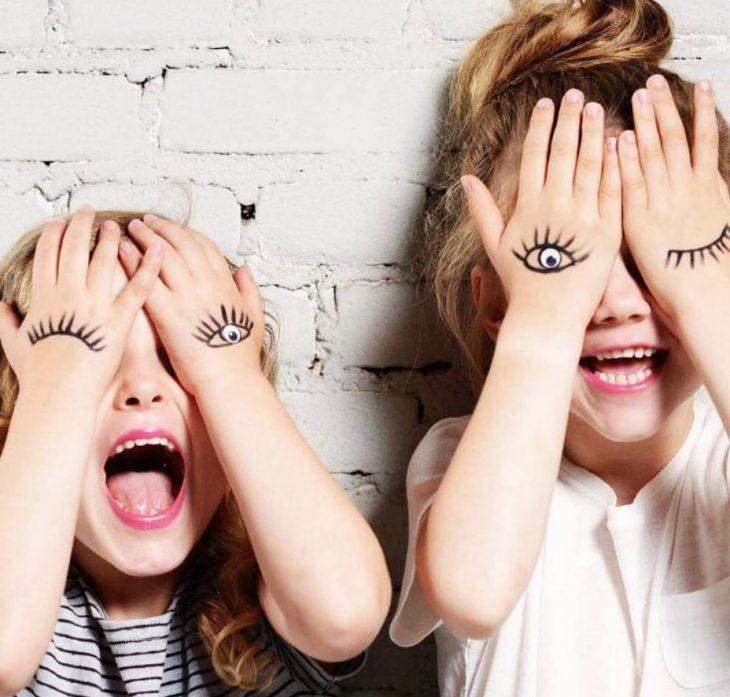 dos niñas con las manos en sus ojos
