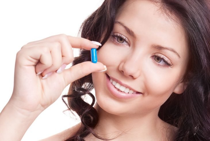 Chica sosteniendo unas vitaminas