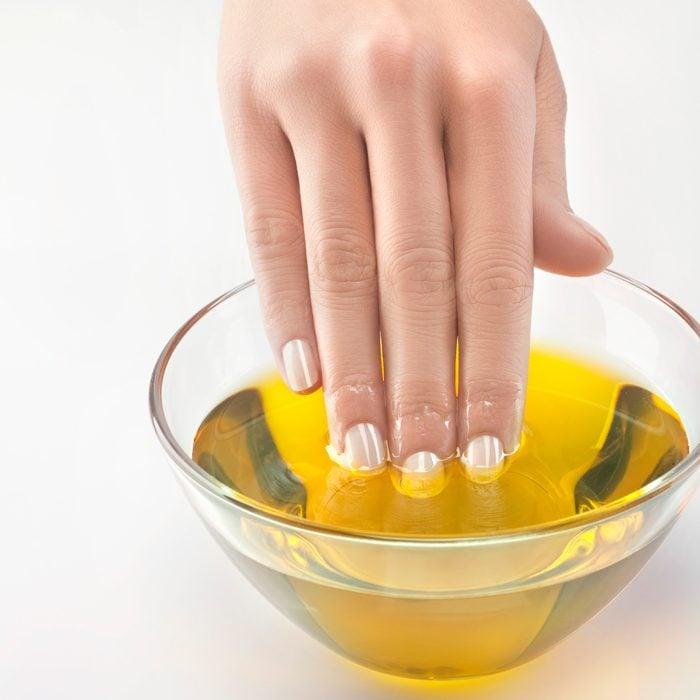 Uñas de una chica remojadas en aceite de almendras