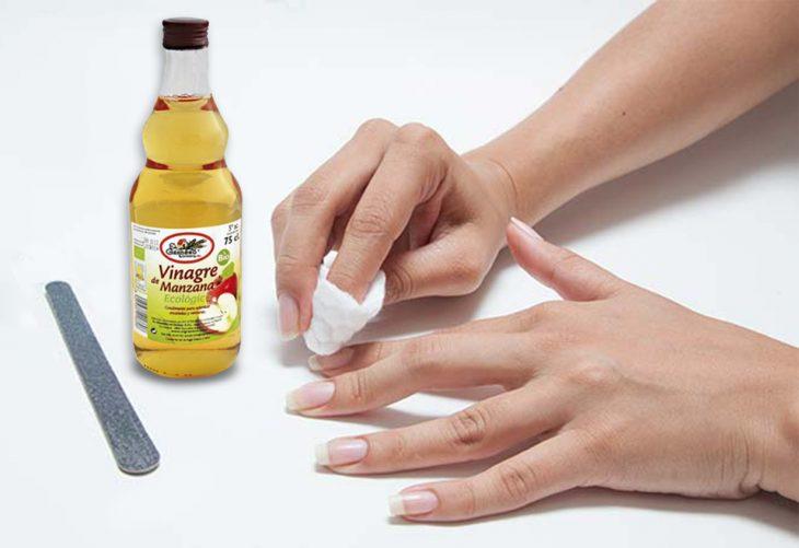 Chica poniendo vinagre sobre sus uñas