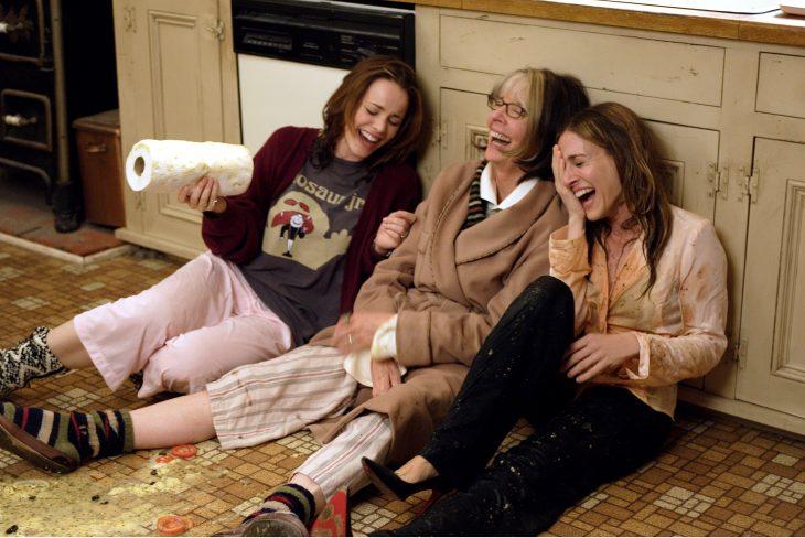 madre con hija y amiga riendo en el piso