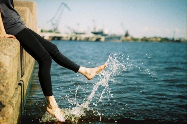 chica con los pies en el mar