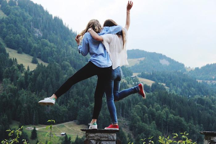chicas abrazadas sobre una piedra