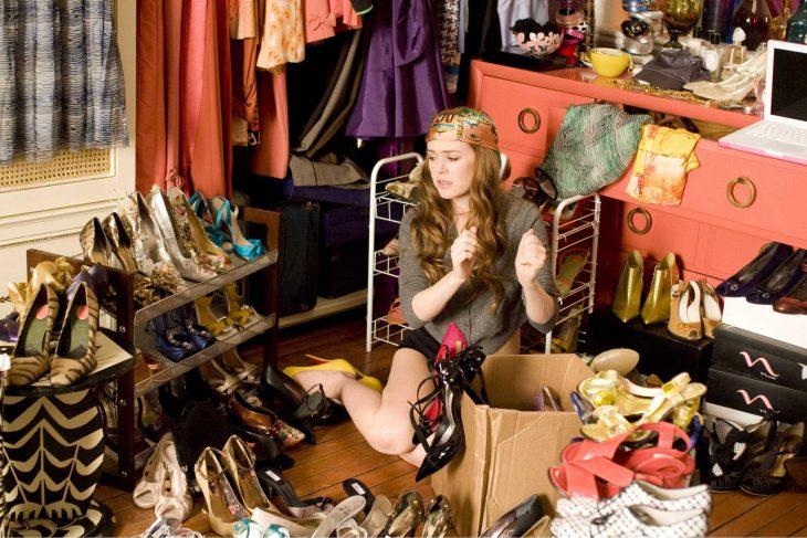 Escena de la película confesiones de una compradora compulsiva. Chica sentada rodeada de zapatos