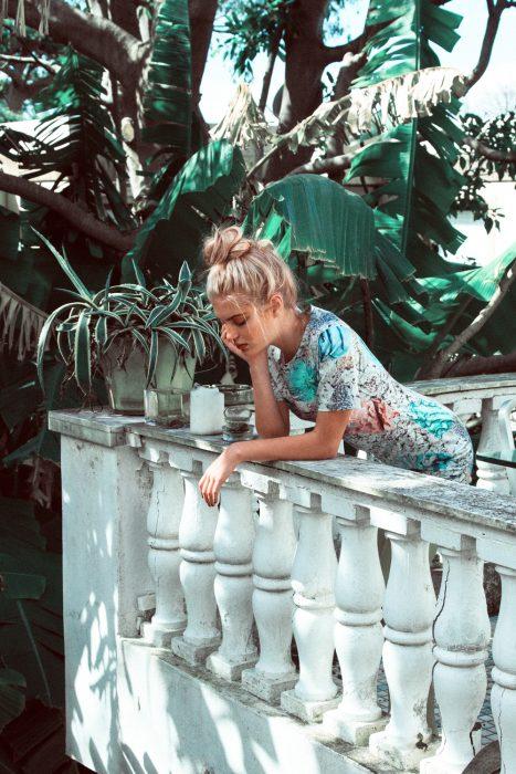 Chica recargada en un balcon pensando