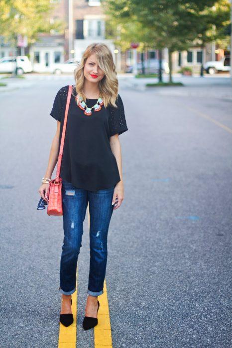 Chica parada en medio de la carretera usando una blusa negra y jeans