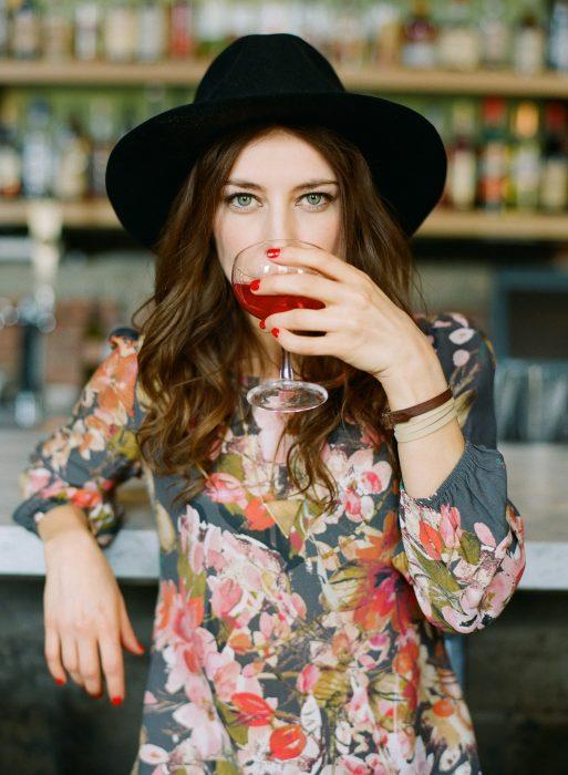 Chica recargada en la barra de un bar bebiendo vino