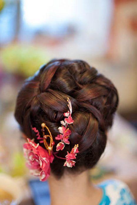 chica con peinado de chongo y flores rosas