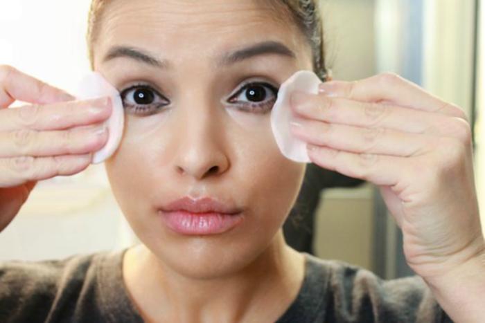 mujer con toallas desmaquillantes en los ojos