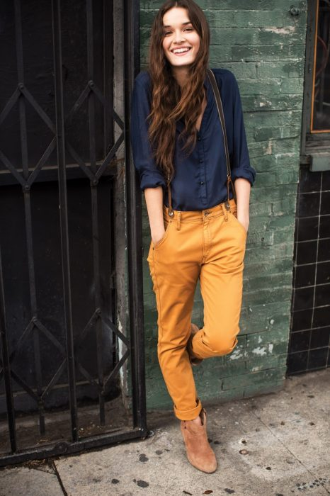 Chica usando una camisa color azul y un pantalón color amarillo mientras está recargada en una pared
