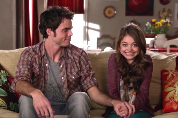 Escena de la serie modern family chica sonriendo sentada en un sofá