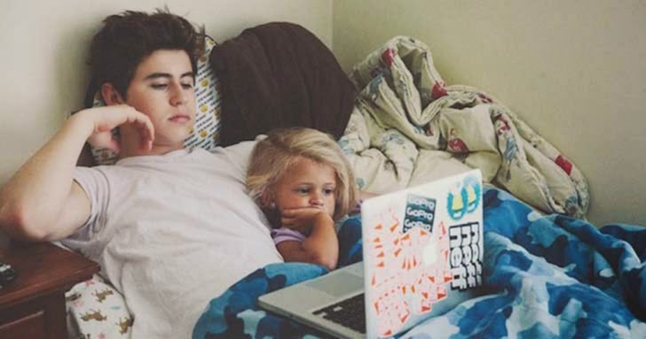 Chico viendo la computadora junto a su hermano
