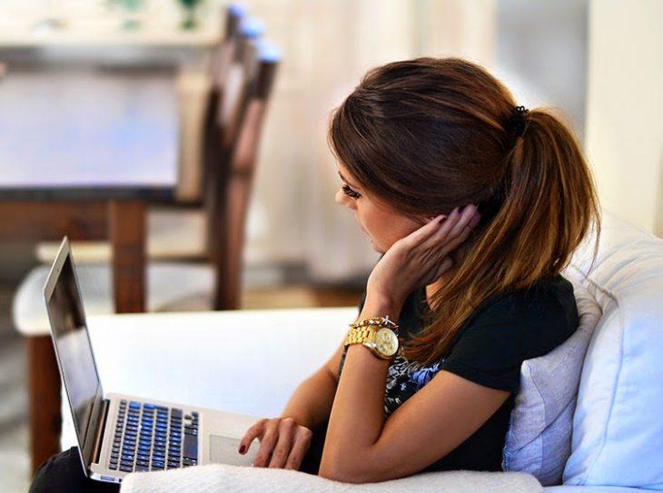 Chica sentada en un sofá revisando su computadora