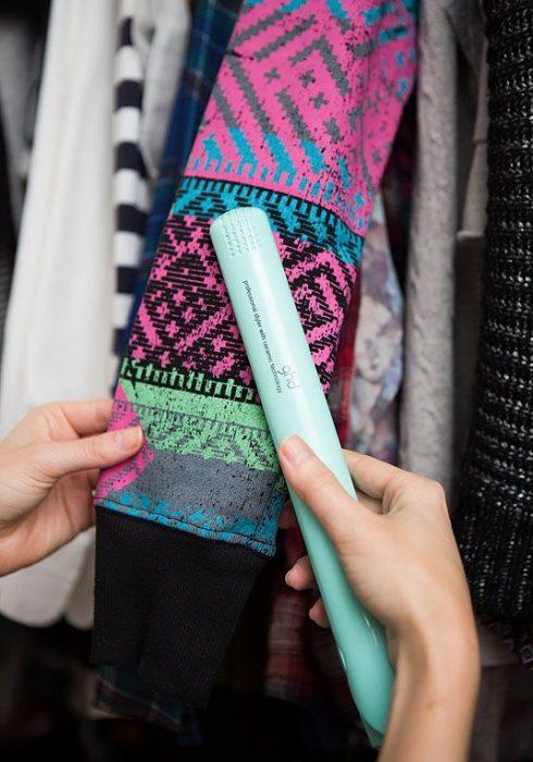 mujer planchando ropa con plancha de cabello