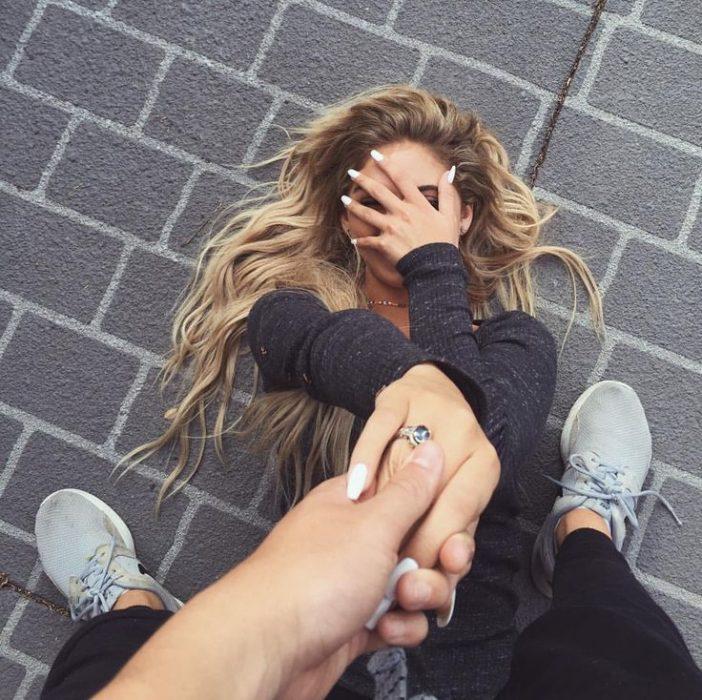 chica en el suelo mientras hombre sostiene su mano