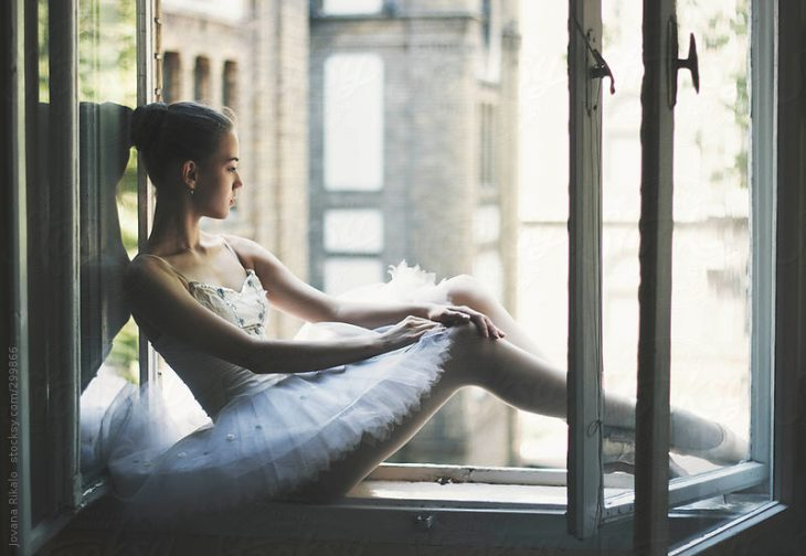 chica con tutu ballerina sentada en la ventana