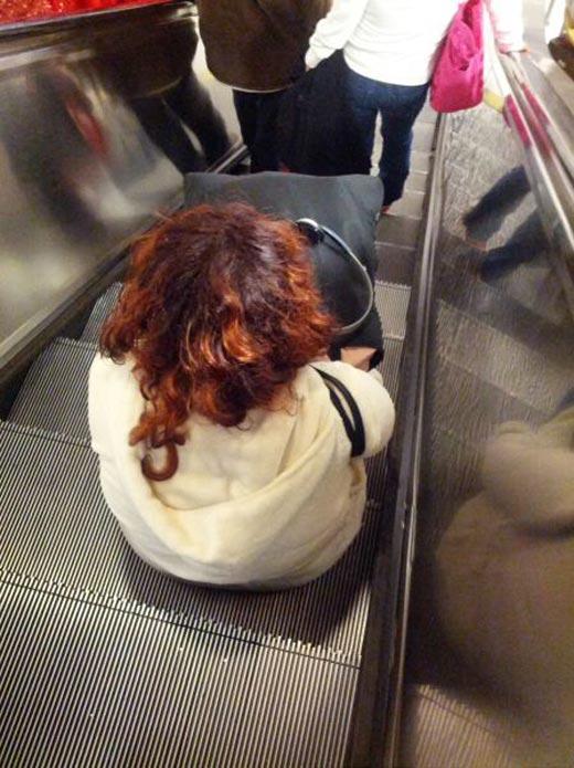 mujer sentada en escalera eléctrica