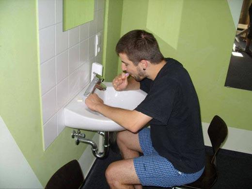 hombre lavándose los dientes sentado frente a lavabo