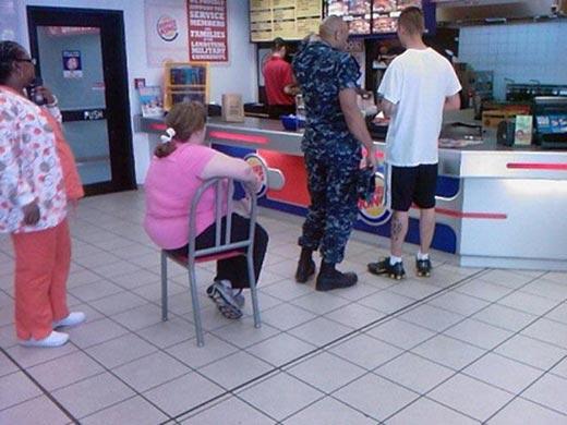mujer sentada en fila de hamburguesas