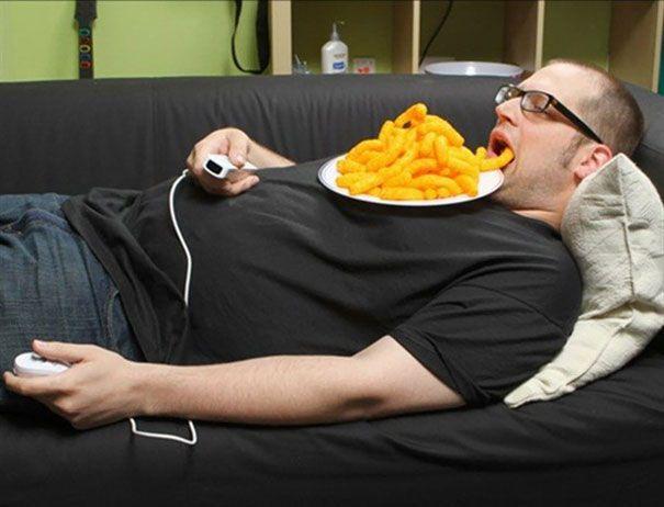 hombre comiendo frituras acostado