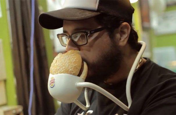hombre come hamburguesa de un soporte especial