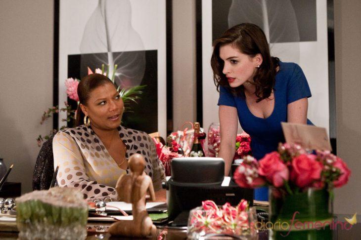 mujer sentada y amiga recargada en escritorio