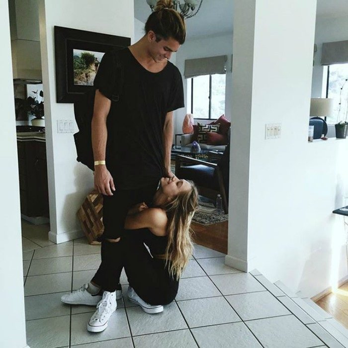 hombre de pie mira a su novia en el suelo abrazandolo