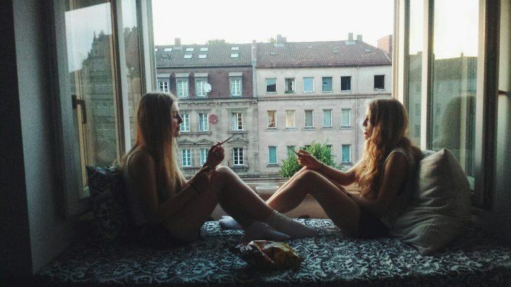 dos mujeres sentada en la ventana fumando