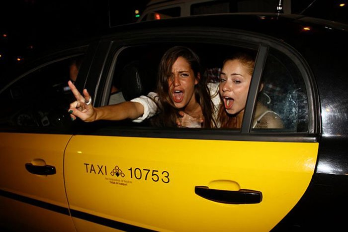 chicas en un taxi gritan felices señal amor y paz