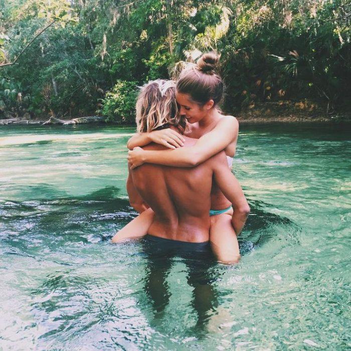 hombre carga a mujer en sus brazos y la abraza