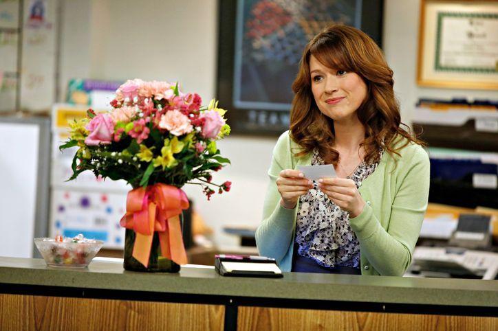 mujer peliroja en escritorio con flores