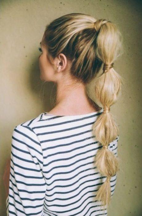 chica con peinado de cola de caballo alta y blusa de rayas