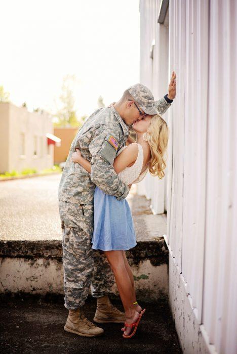 Hombre vestido de militar besando a una chica