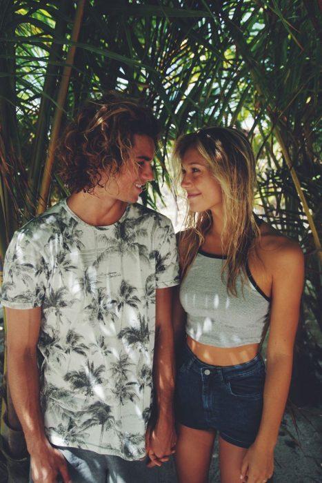 Pareja de novios en la playa viéndose uno al otro