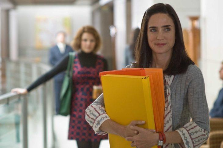 mujer con carpetas sonriendo en oficina
