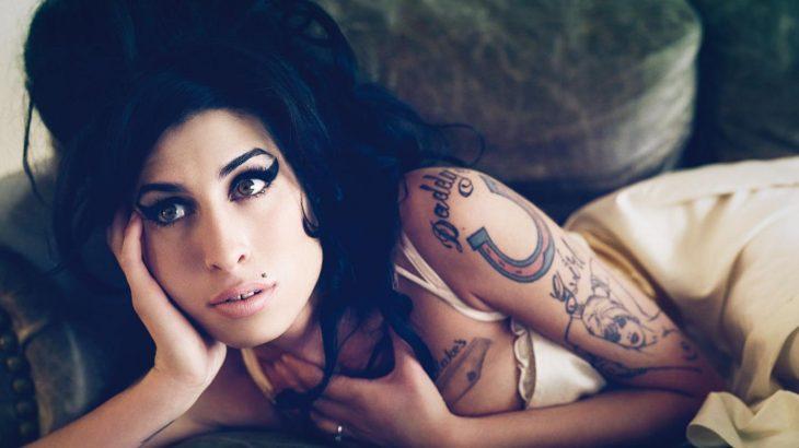Cantante Amy Winehouse recostada en un sofá
