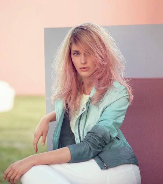 Chica con el cabello en color rosa-dorado sentada en un jardín