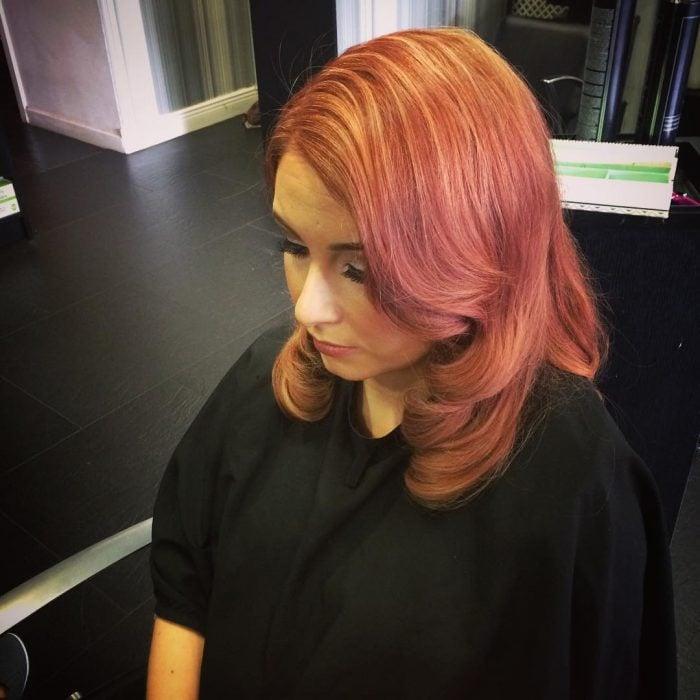Chica con el cabello hasta los hombros pintado en color rosa con dorado y toques rojizos