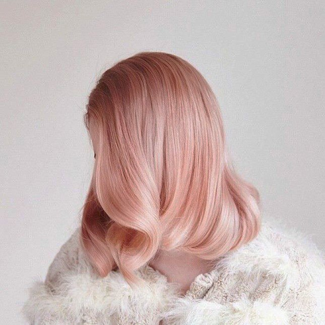 Chica peinada como en lso años 40 usando el cabello color rosa-dorado
