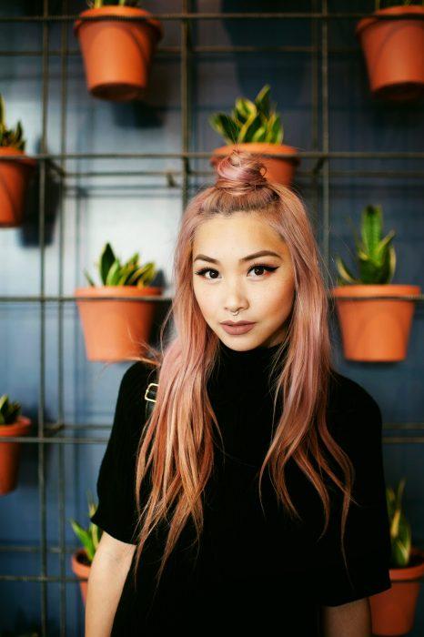 Chica con el cabello sujetado en un halfbun y pintado de color rosa-dorado