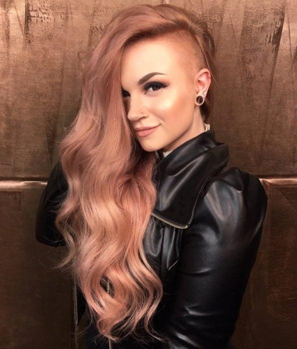 Chica con el cabello pintado en color rosa-dorado y rapada de un lado
